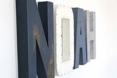 Nautical nursery letters in blues and white spelling out Noah.