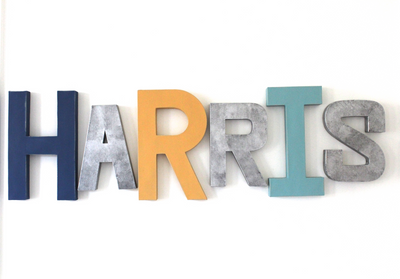 Name wall letters spelling out Harris in blues, yellows, and navy for toddler boy room decor.