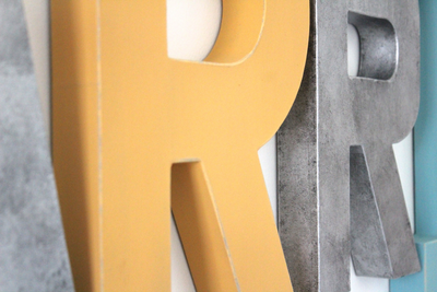 Name wall letters in mustard yellow and silver colors.