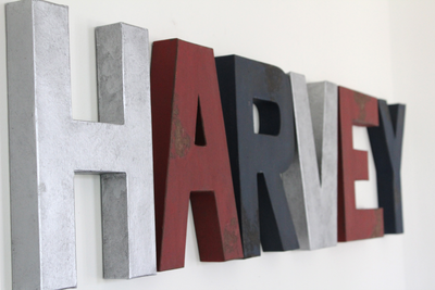 Sports nursery theme letters spelling out Harvey in silver, red, and navy letters.