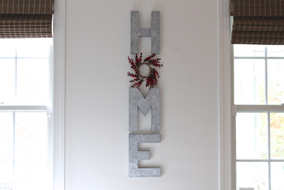 Rustic home wall letters with a red wreath instead of the letter O.