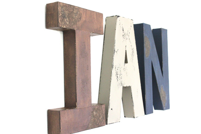 Distressed wall letters spelling out Ian in brown, gray, and navy for woodland themed nurseries.
