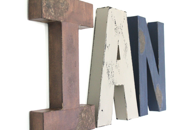 Nursery name signs for a boys mountain nursery wall decor spelling out Ian in different distressed colored letters.