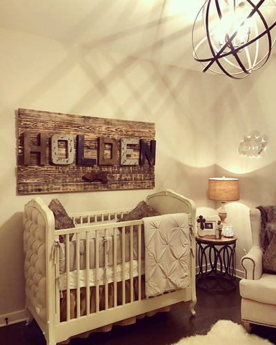 A modern rustic nursery with distressed wall letters spelling out Holden in brown, gray, and black.