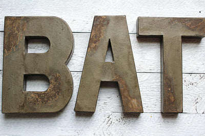 Distressed bath sign in a gray taupe color.