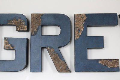 Navy blue distressed wall letters G, R, and E.
