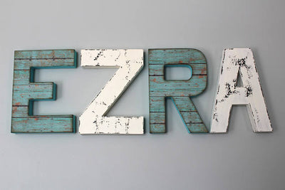 Gender neutral nursery letters spelling out Ezra in teal and white colors.