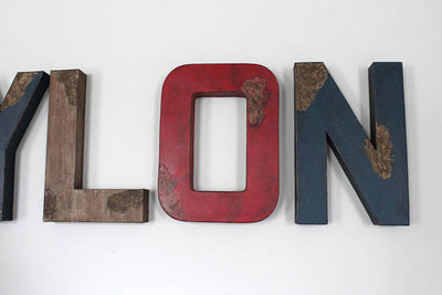 Distressed red, brown, and navy custom wall letters for a woodland animal nursery.