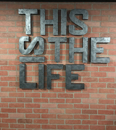 This is the Life sign in grey on a brick wall