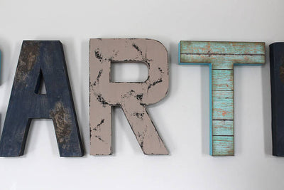 Distressed wall letters in navy, gray, and teal/aqua.