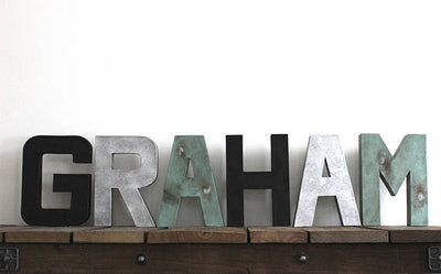 Industrial farmhouse name letters for boys room wall decor spelling out Graham in three different colors and textures.