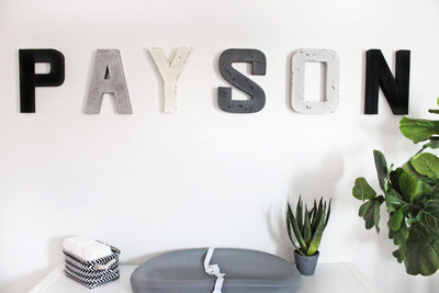 Monochromatic girls nursery decor letters spelling out PAYSON in gray, black, white, and silver.