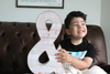 "Pink ""wooden"" ampersand sign being held by a smiling boy with dark hair."