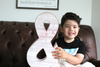 "Little boy holding a large pink ""wooden"" ampersand."