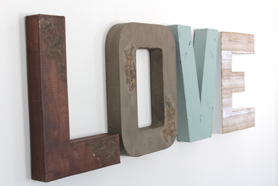 Love wall letter sign in brown, gray, white, and blue.