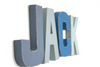 "Blue ""wooden"" letters spelling out the name JACK in different shades of blue."