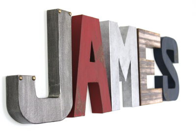 Boy nursery decor custom wall letters spelling out James in different industrial and rustic textures and colors.
