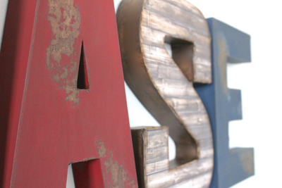 Distressed nursery wall letters in red, brown, and navy.
