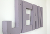 Purple girl's room name sign spelling out JEAN.