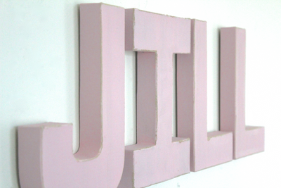 "Pink slightly distressed ""wooden"" nursery wall letters spelling out a girl's name Jill."
