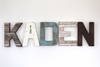 brown, white, and blue wooden letters spelling out KADEN for baby boy nursery