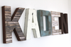 Custom wall letters for boy nursery wall decor spelling out the name Kaden in different faux wood textures and colors such as brown, blue, and white.