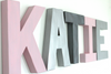 Pink and silver girl name sign spelling out KATIE.