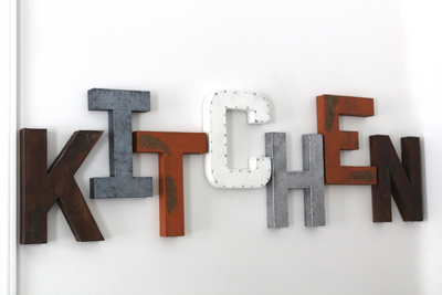 Farmhouse kitchen wall letters in brown, orange, silver, gray, and white.