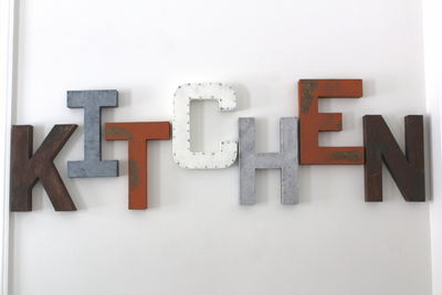 Farmhouse kitchen wall letters in different colors and textures.