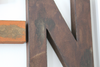 "Brown distressed ""wooden"" letter N."