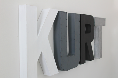 Monochrome nursery letters in black, gray, and black spelling out the name Kurt.