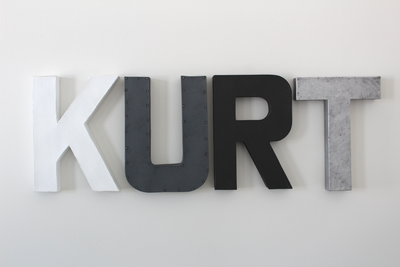Modern nursery name letters spelling out the name KURT in white, gray, black, and silver letters.