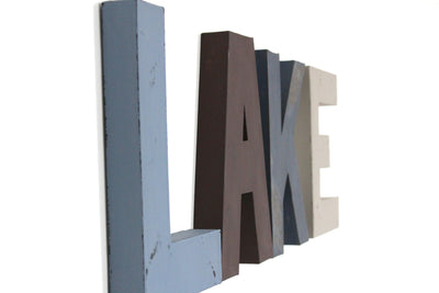 "Lake house sign in blue and brown ""wooden"" wall letters."