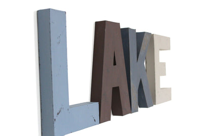Lake home wall decor and lake home wall letters in different styles and shades of blue and brown.
