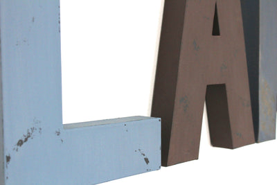 "Blue ""wooden"" wall letters and brown ""wooden"" wall letter A."