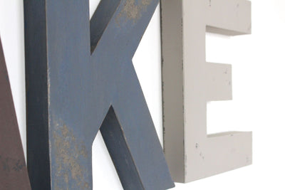"Distressed ""wooden"" navy wall letter K and gray ""wooden"" letter E."