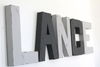 Modern boys room name letters spelling out LANCE in dark and light grey colors.