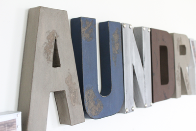 "Distressed ""wooden and ""metal"" letters spelling out the word laundry."