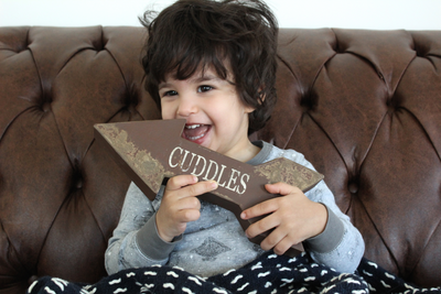 Cute little boy sitting on a sofa holding wooden arrow for picture prop.