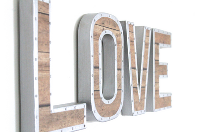 Love wall sign with a nail trim surrounding the letter.