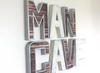 Man cave wall letters in silver and white with nail trim designs around each letter.