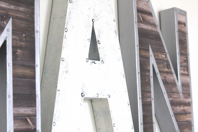 Rustic industrial letters in white and silver with a nail trim design.