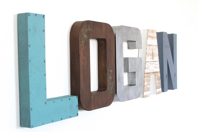 Wall letters for baby boy nursery decor in different shades of blue, brown, and silver spelling out the name Logan.
