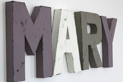 """Wooden"" nursery letters spelling out Mary in purple, white, and gray."