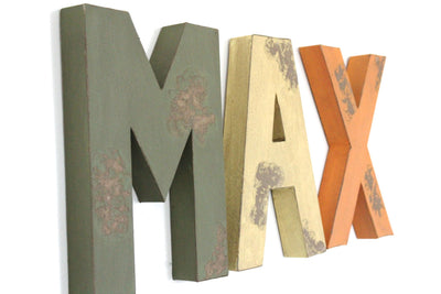 Distressed letters spelling out Max for safari themed nursery decor.