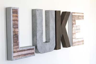 Industrial nursery letters spelling out Luke in brown, bronze, silver, and whites.