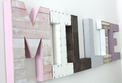 "Pink ""wooden"" and ""metal"" wall letters spelling out the name MILLIE."