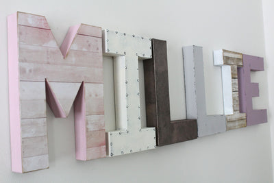 Millie girl's name wall letters in shades of pink, white, and gray.
