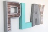 Mint playroom wall letters in different colors and textures spelling out the word PLAY.