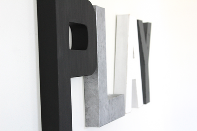 Modern play letters in black, white, and silver.
